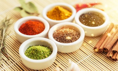 Various colorful spices in bowls on wooden table