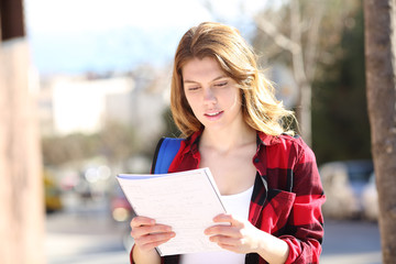 Student studying walking in the street