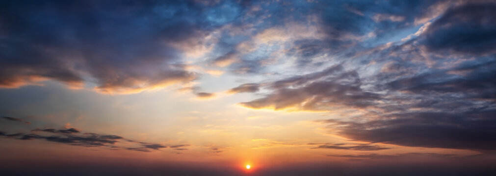 Dramatic sunset and sunrise sky. Orange, blue and yellow colors sunset. Panoramic view.