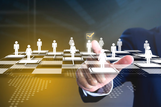 Business administrator selecting a man in action of manpower or human resource planning or business organisation on a virtual checkerboard or draughtboard.