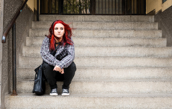 Homeless girl, Young beautiful red hair girl sitting alone outdoors on the stairs of the building with hat and shirt feeling anxious and depressed after she became a homeless person