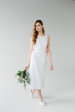 attractive woman in elegant dress walking with flowers on grey