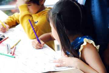 Kids boy and girls learning drawing on white paper in holiday weekend.