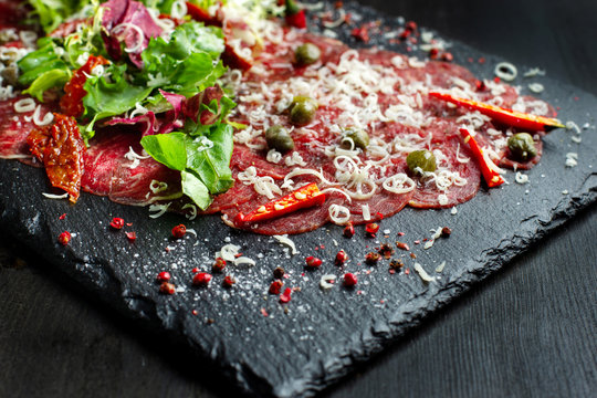 Beef carpaccio on black plate with mustard and parmesan.