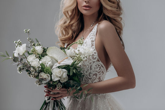 beautiful sexy blonde bride posing in a sparkling wedding dress with bouquet. advertising space