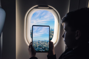 Caucasian boy using tablet pc taking picture through airplane window San Francisco cityscape. California. USA