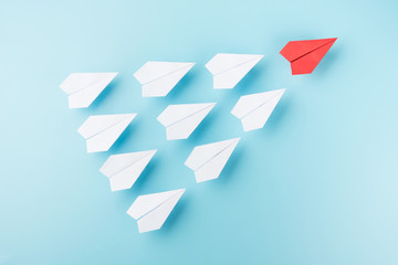 Group of white paper plane and one red plane isolated on blue background business leader teamwork growth concept photo object design