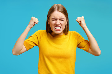Aggression girl with widely open mouth and clenched teeth holds hands clenched in fists. Photo of girl in yellow sweater on blue background. Emotions and feelings concept