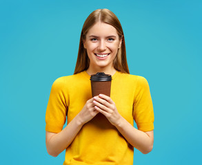 Young girl holds paper cup with hot coffee, takeaway. Photo of attractive girl in yellow sweater on blue background