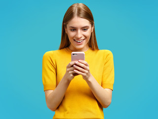 Happy girl with surprised expression looks at the phone. Photo of girl in yellow sweater on blue background.
