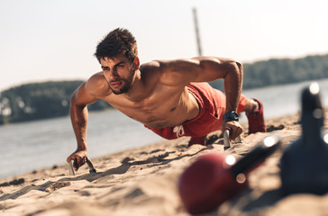 Young man doing fitness workout at a beach on a sunny day.