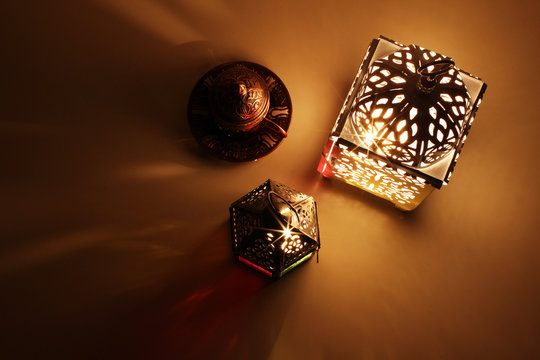 Festive table composition of glowing Moroccan ornamental lanterns and bronze tea cup. Decorative golden shadows. Greeting card, invitation for Muslim holy month Ramadan Kareem. Flat lay, top view.
