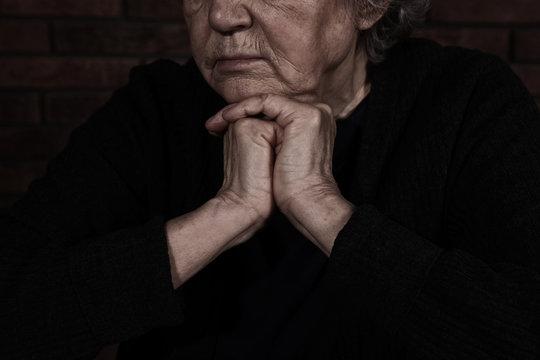 Poor mature woman on dark background, closeup