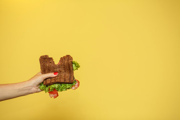 Foto op Canvas Snack woman hands hold bitten sandwich on yellow background. Sandwich promotion concept