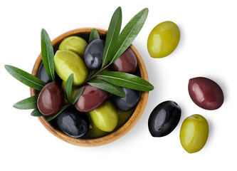 Delicious black, green and red olives with leaves in a wooden bowl, isolated on white background, view from above