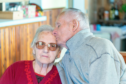 Elderly couple kissing at home. Retirement and love concept