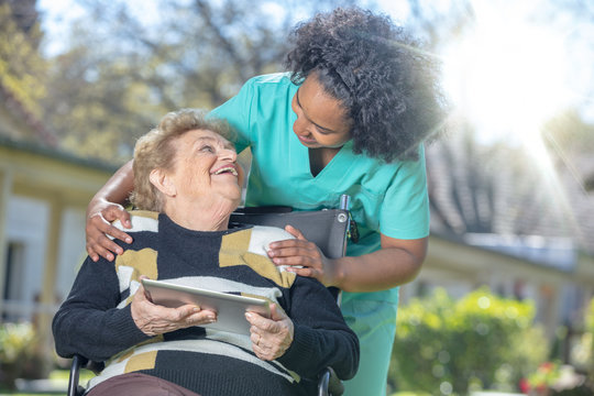 African female doctor playing and smiling with mature elderly woman on wheelchair in the garden using tablet