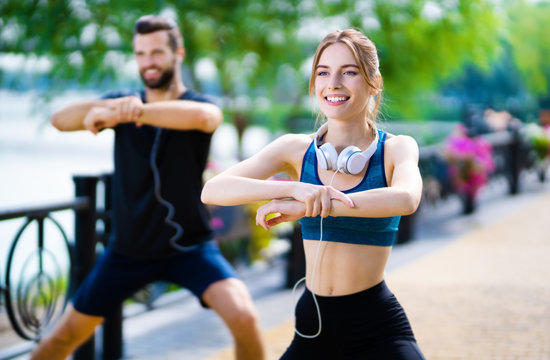 Happy couple doing exercises together, outdoors