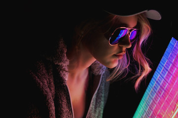 Portrait of the Beautiful Young Pro Gamer Girl. Attractive Girl with Glasses by Neon Lights.