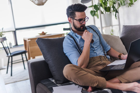 Young bearded businessman is sitting on sofa working with laptop computer. Freelancer, entrepreneur works at home.