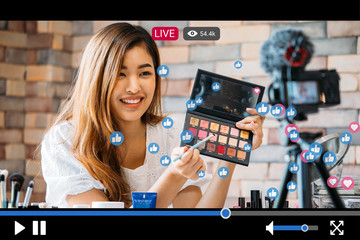 Young beautiful woman recording live stream video for makeup and cosmetics business purpose online with video player interface amd full of positive feedbacks