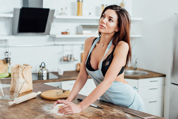 Sexy woman in underwear and blue apron kneading dough in kitchen