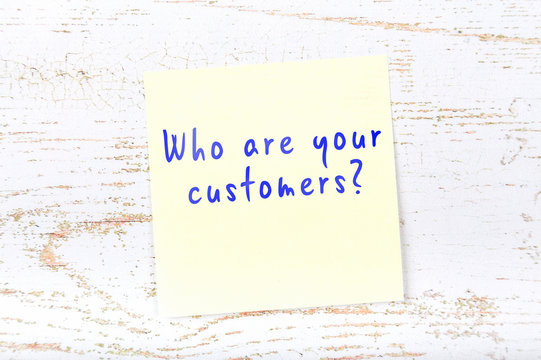 Yellow sticky note with handwritten text who are your customers