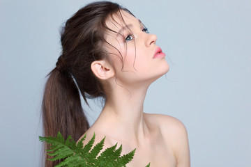 Beautiful  girl with fern leaf, isolated on a light - grey  background, emotions, cosmetics