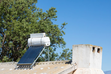 Small solar hot water geyser and photovoltaic panel on a rural farm laborers cottage supplying renewable energy for heating and electricity