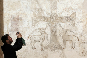 A tourist takes a photo of decorative paintings on the walls the Coptic Orthodox Red Monastery, established in the 4th century in Sohag