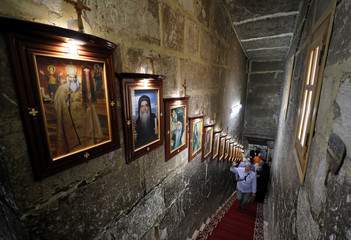 Tourists walk up the stairs next to a series of religious photos inside the Coptic White Monastery, founded in 442 AD in Sohag