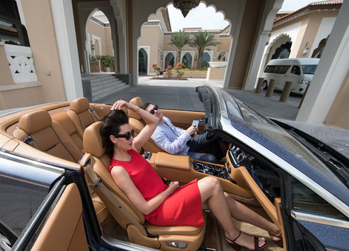 a rich woman and a man in a cabriolet