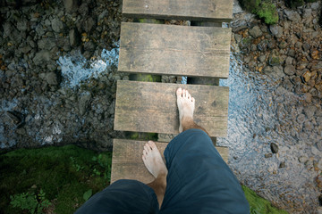 Barefoot person crossing narrow wooden bridge in the forest. Personal perspective used.