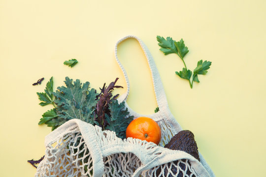 white eco-friendly textile string bag with fresh fruits, herbs and vegetables isolated on yellow background, plastic free shopping, healthy eating