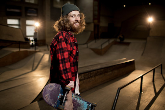 Waist up portrait of long haired man holding skateboard looking at camera standing in extreme sports park, shot with flash