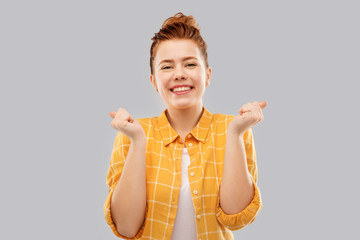 achievement, emotions and people concept - happy smiling red haired teenage girl in checkered shirt celebrating success over grey background