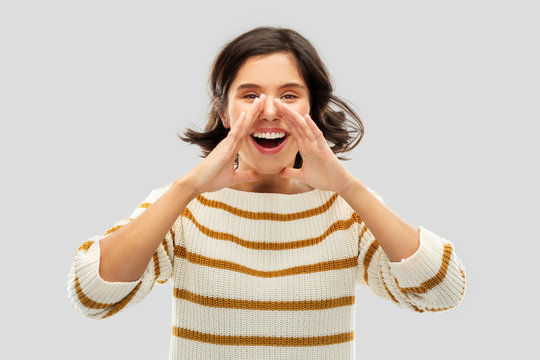 people concept - happy smiling young woman in striped pullover calling someone over grey background