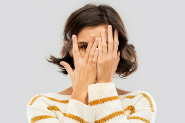 people concept - happy smiling young woman in striped pullover closing face with hands and looking by one eye through her fingers over grey background Wall mural