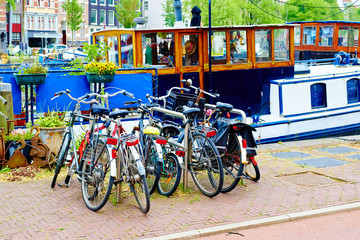 Bicycles parked on street in Amsterdam in rainy day, The Netherlands