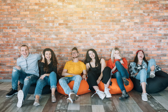 Millennials hanging out in lounge zone. Young people resting in bean bags, having fun together, enjoying break at work.