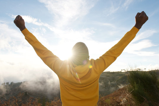 back of african american man in hoodie with hands raised in air and sun in background
