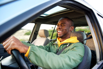 Side of happy african american man driving car
