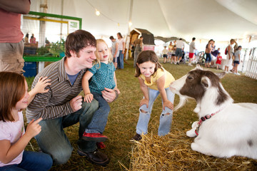 Family Looking at a Goat at Agricultural Fair