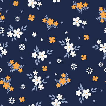 Vintage floral background. Seamless vector pattern for design and fashion prints. Flowers pattern with small white and yellow flowers on a dark blue background. Ditsy style