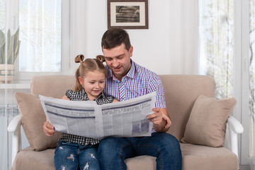 Little daughter and dad sitting on the sofa at home and reading the newspaper together