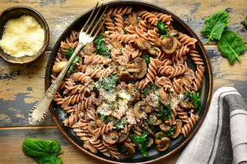 Whole wheat fusilli pasta with mushroom and spinach.Top view with copy space.