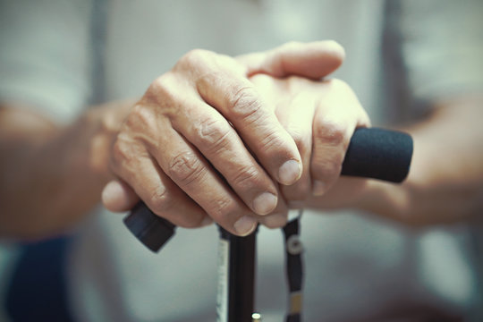 Senior Man Holding Cane. Close-up Of old man Hands On Walking Stick. Hand of a old man holding a cane. Toning.