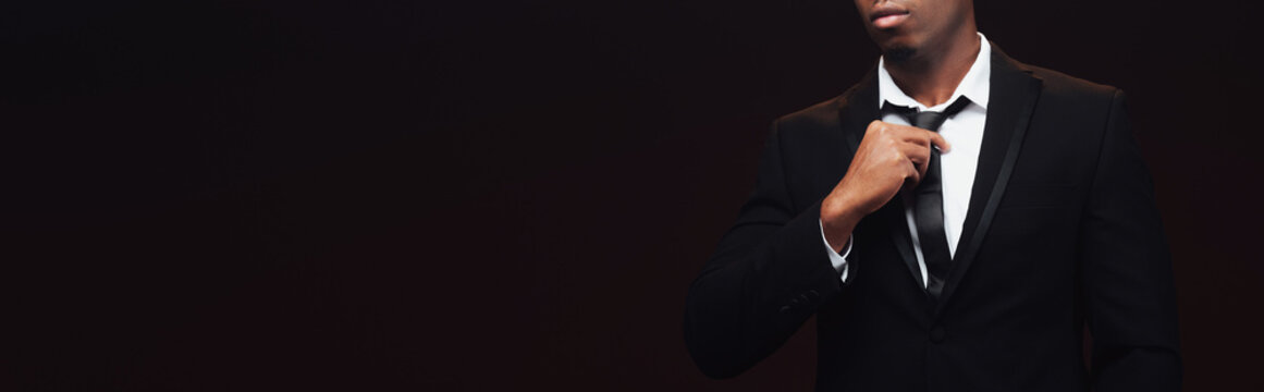 cropped view of fashionable african american man in suit adjusting tie isolated on black with copy space