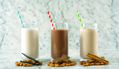 Nutritious vanilla, chocolate and cinnamon almond milk in glasses.
