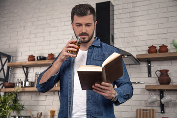 handsome young man is drinking an apple juice and reading a book at the kitchen